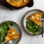 Two servings of baked frittata served with a side salad. A cast iron skillet with the remaining frittata sits off to the side.