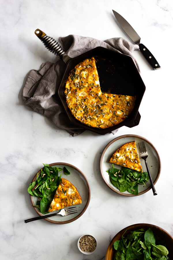 A sausage, kale, and sun-dried tomato pesto frittata baked in a cast iron skillet. Two ceramic plates with a serving of frittata and a side salad sit nearby.