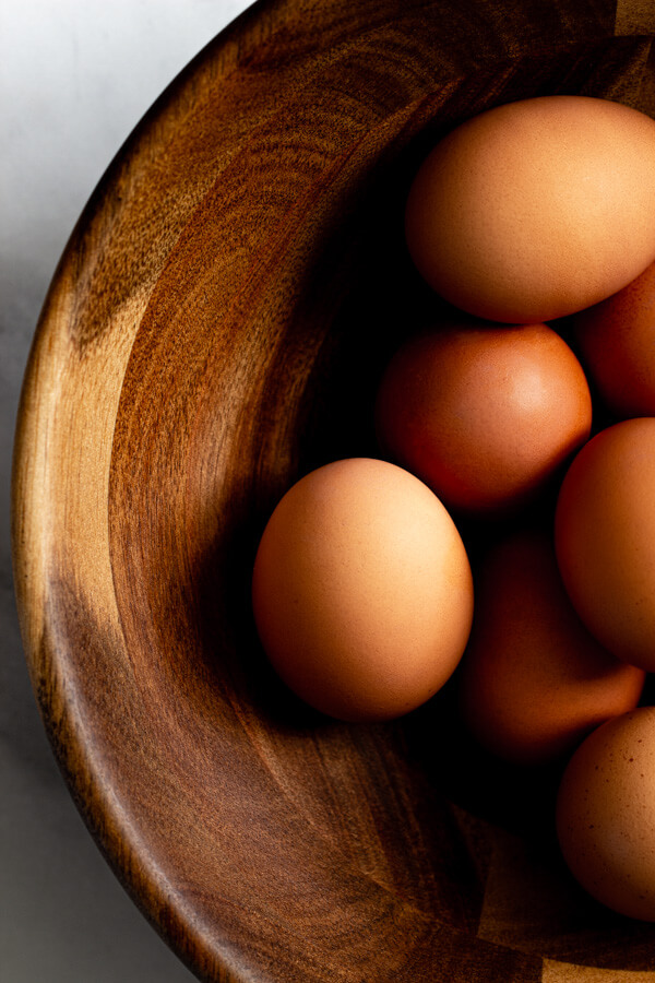 A wooden bowl holding brown eggs.