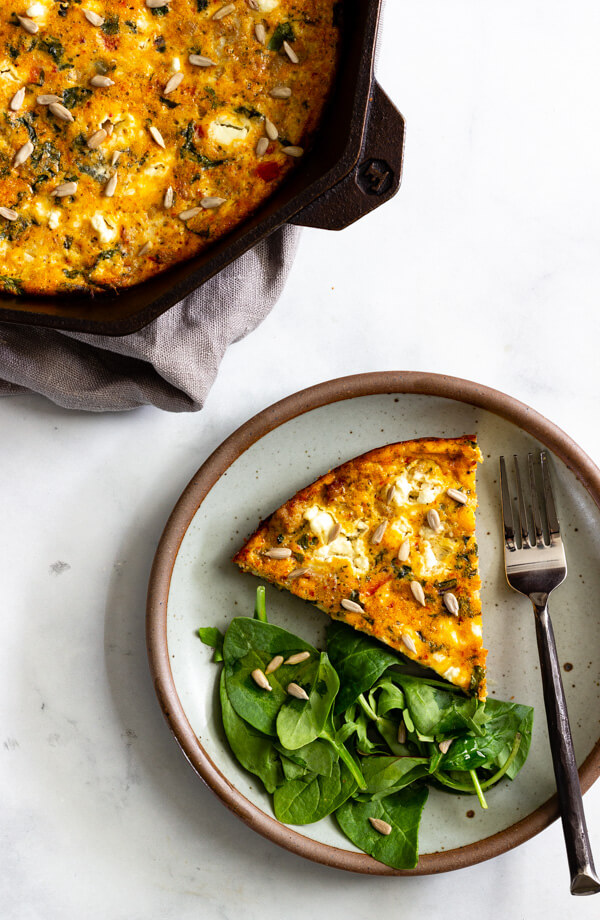 A wedge of baked frittata topped with a sprinkling of sunflower seed kernels is served on a ceramic plate with a spinach side salad.