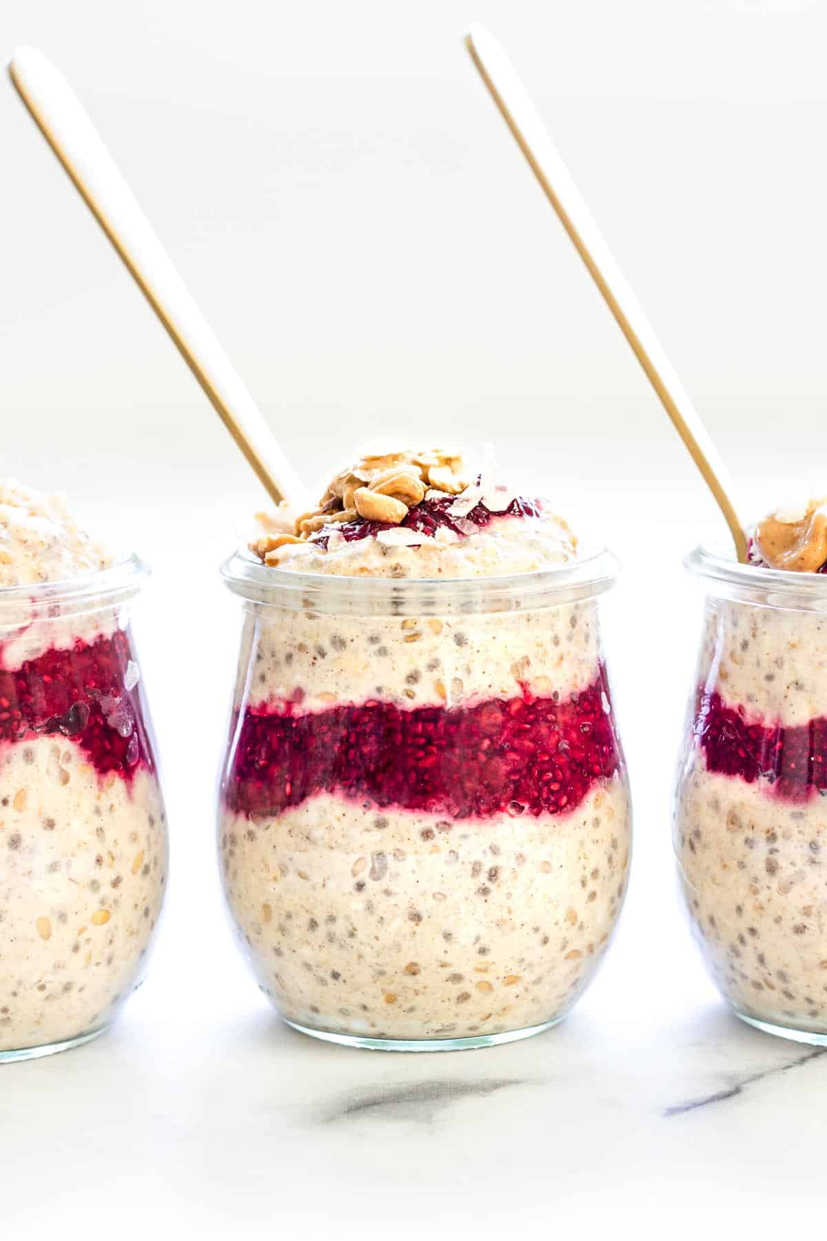 Three jars of healthy overnight oats topped with chopped peanuts, berry chia jam, toasted coconut flakes, and a drizzle of peanut butter.
