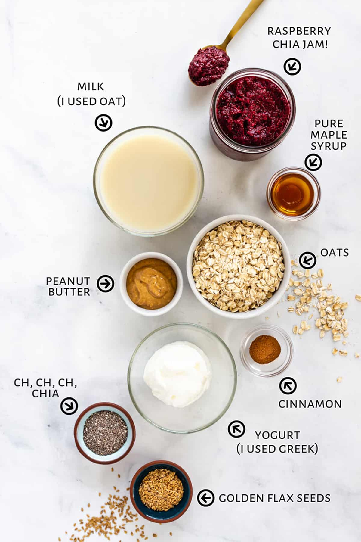 All of the ingredients for the overnight oats are setout in little bowls on a white countertop.