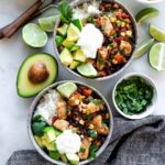 Two bowls of southwest chicken and rice topped with cilantro, avocado, and sour cream. Served with lime wedges.