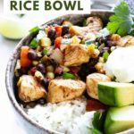 A close-up view of a comforting southwest chicken rice bowl topped with avocado, sour cream, and cilantro.
