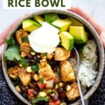 Two hands holding a delicious southwest chicken rice bowl topped with avocado, sour cream, and cilantro.