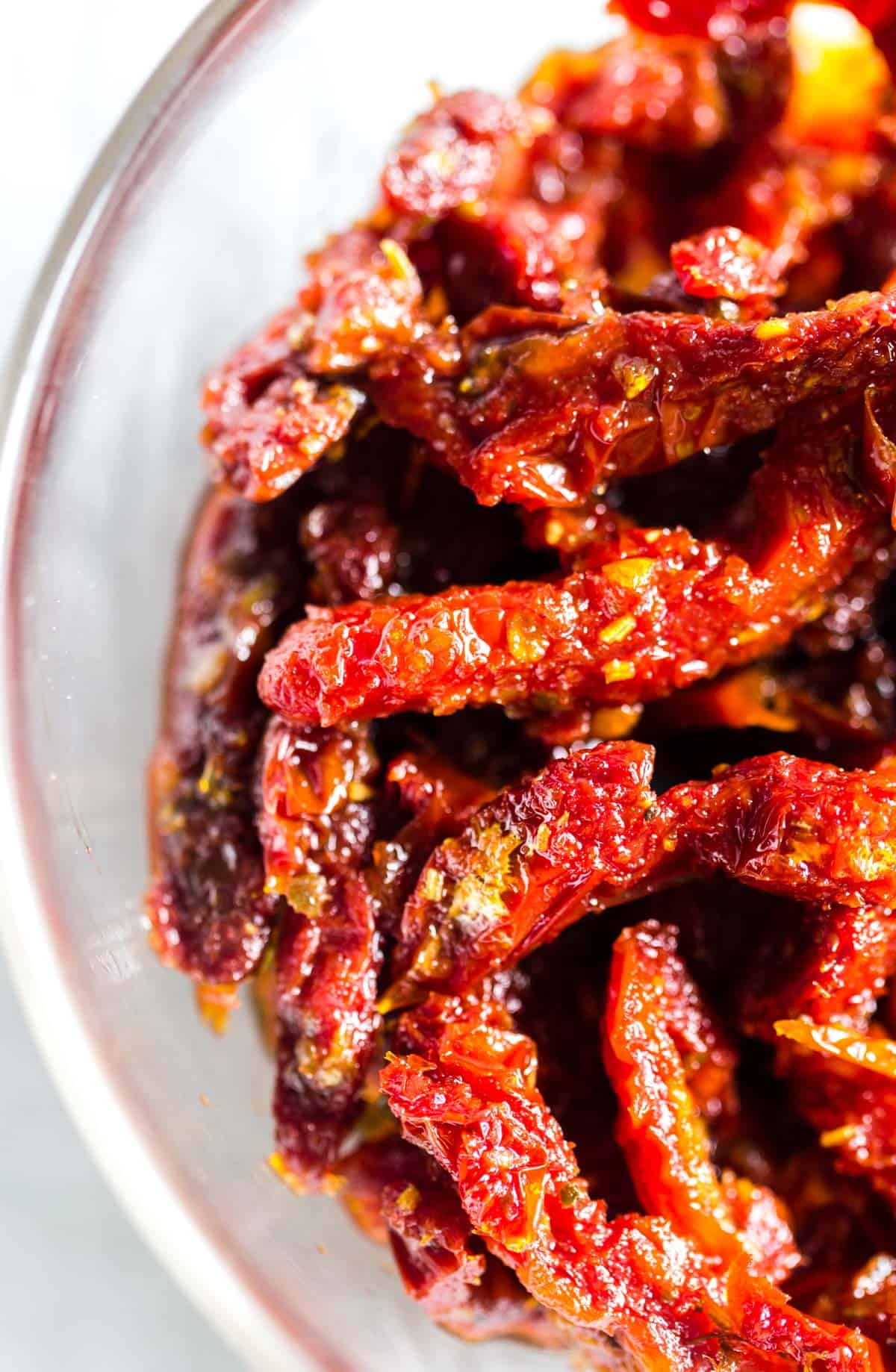 A close-up of bright, red sun-dried tomatoes in oil.