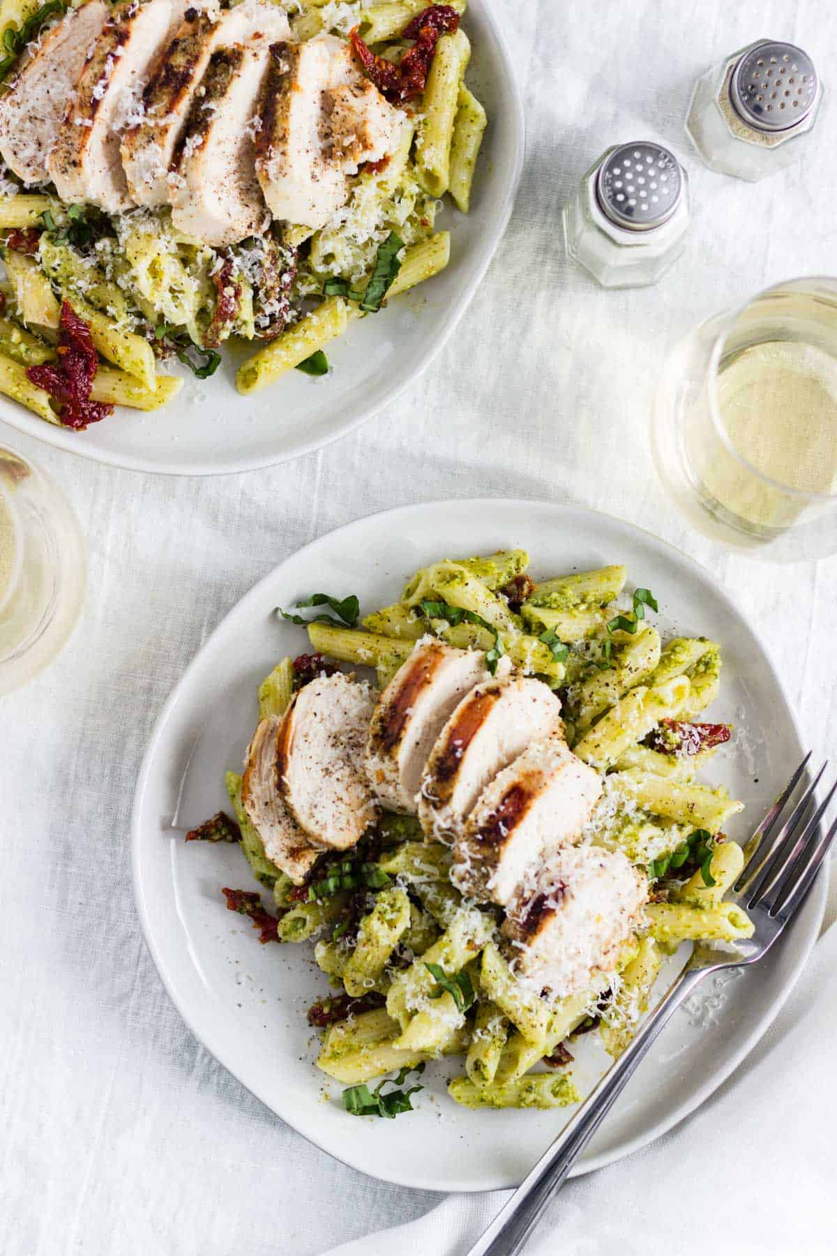 Two plates of creamy pesto pasta with chicken and sun-dried tomatoes on a white tablecloth. Two glass of white wine sit nearby.