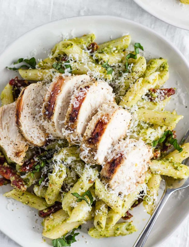 A plate of creamy pesto pasta with chicken and sun-dried tomatoes.