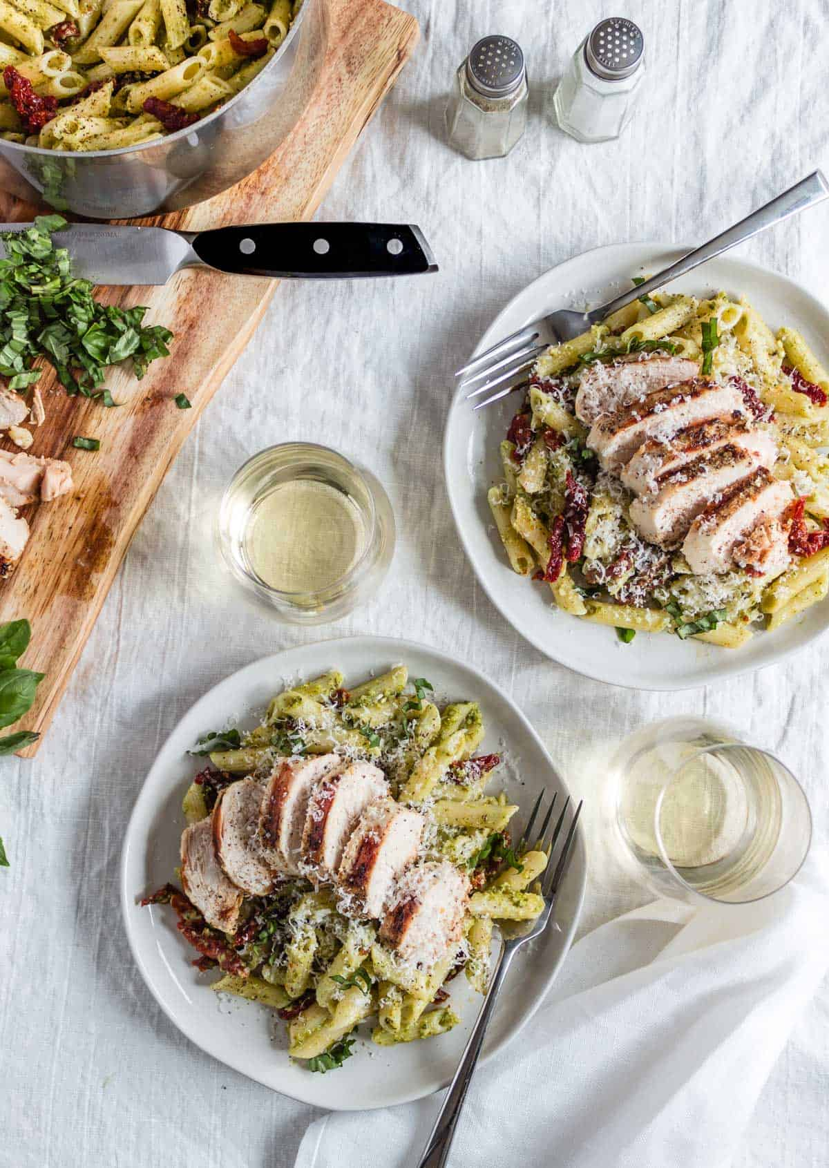 Two plates of creamy pesto pasta topped with grilled chicken, sun-dried tomatoes, and grated parmesan. Two glasses of white win sit nearby as well as a pot of pasta seconds and a serving board with sliced grilled chicken.