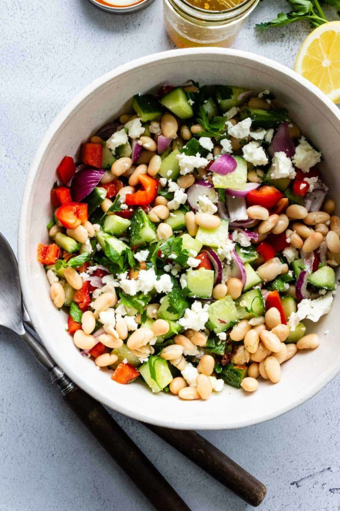 A large bowl of Mediterranean Bean Salad with serving utensils, lemon, and a jar of leftover vinaigrette off to the sides.