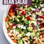 A large bowl of Mediterranean Bean Salad with chopped cucumbers, red bell pepper, sliced red onion, fresh parsley, crumbled feta, and white kidney beans.