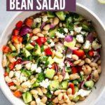 A large bowl of Mediterranean Bean Salad with serving utensils, lemon, and a jar of leftover vinaigrette off to the sides.