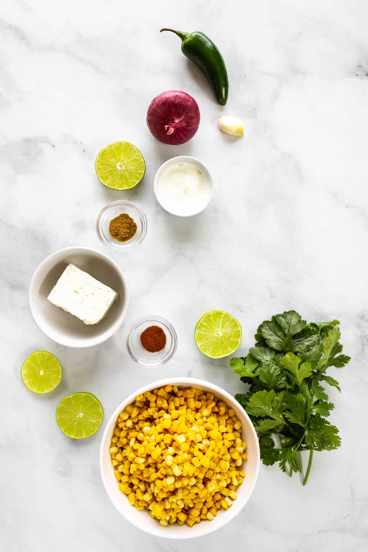 A bowl of corn sits on a marble countertop with some limes, cilantro, a block of feta, a red onion, a jalapeño, a garlic clove, a small bowl of greek yogurt, and two smallpinch bowls of cumin and chili powder.