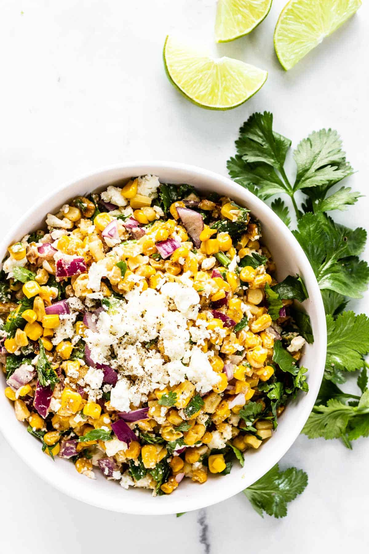 A white serving bowl with Mexican street corn salad is topped with some extra feta. Some cilantro and lime wedges are on the counter nearby.