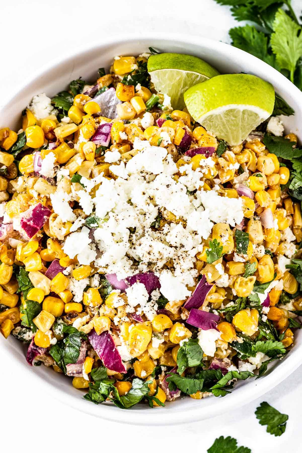 A large serving bowl of Mexican Street Corn Salad is topped with extra crumbled feta and a few lime wedges.