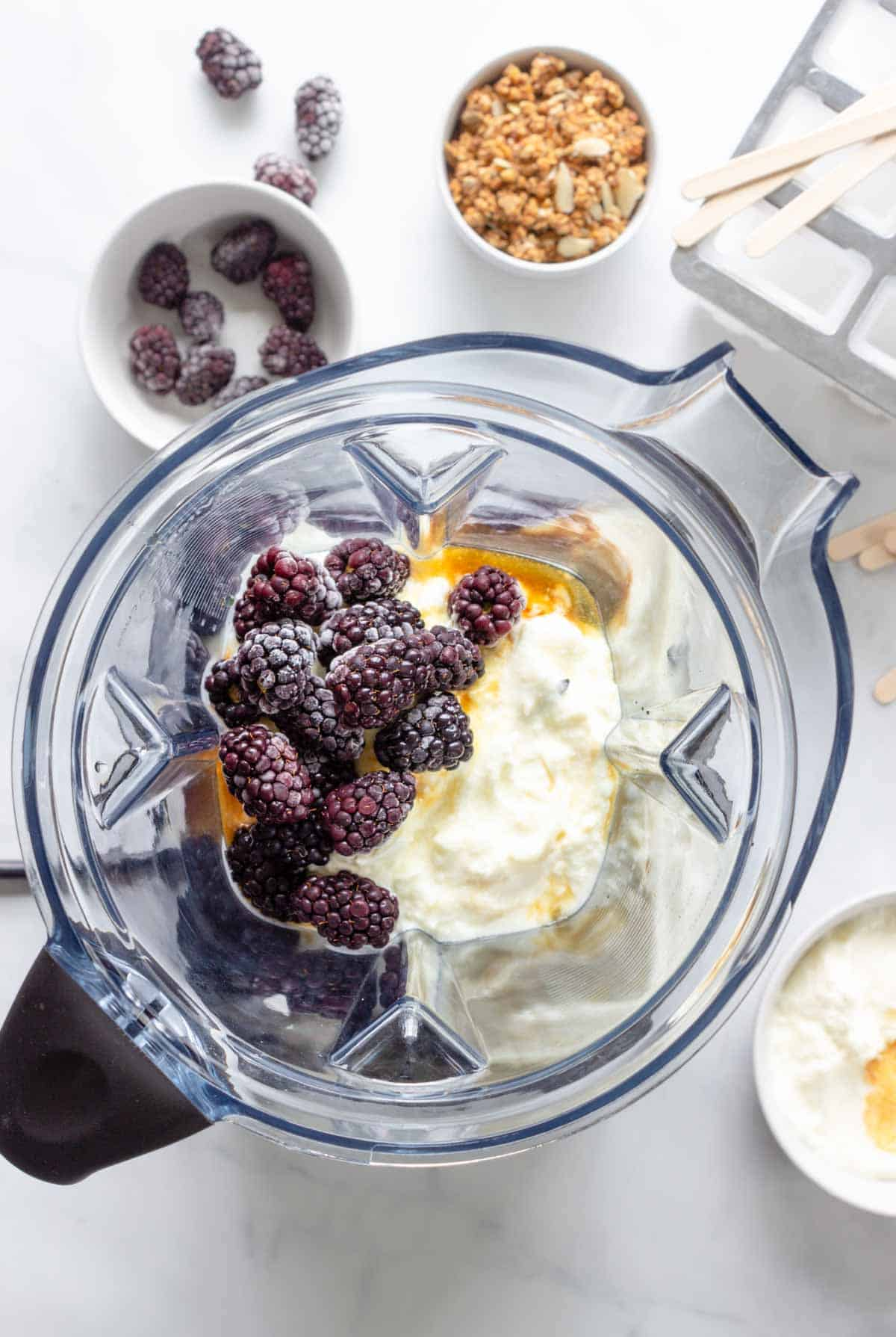 Yogurt, blackberries, maple syrup, and vanilla are placed in a high speed blender. A popsicle tray and sticks along with some granola, blackberries, and yogurt sit nearby.