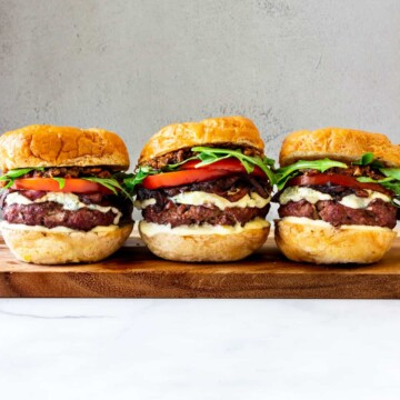 Three bacon blue cheese burgers are lined up next to each other on a wooden plank.