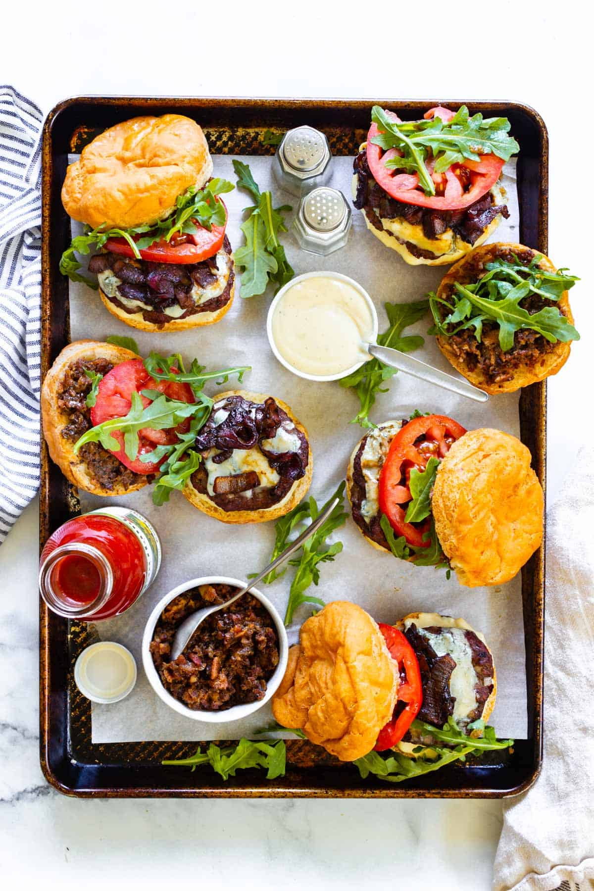 A tray loaded with bacon blue cheese burgers and small side dishes with roasted garlic aioli and bacon jam. A salt and pepper shaker and a ketchup bottle also accompany the burgers.
