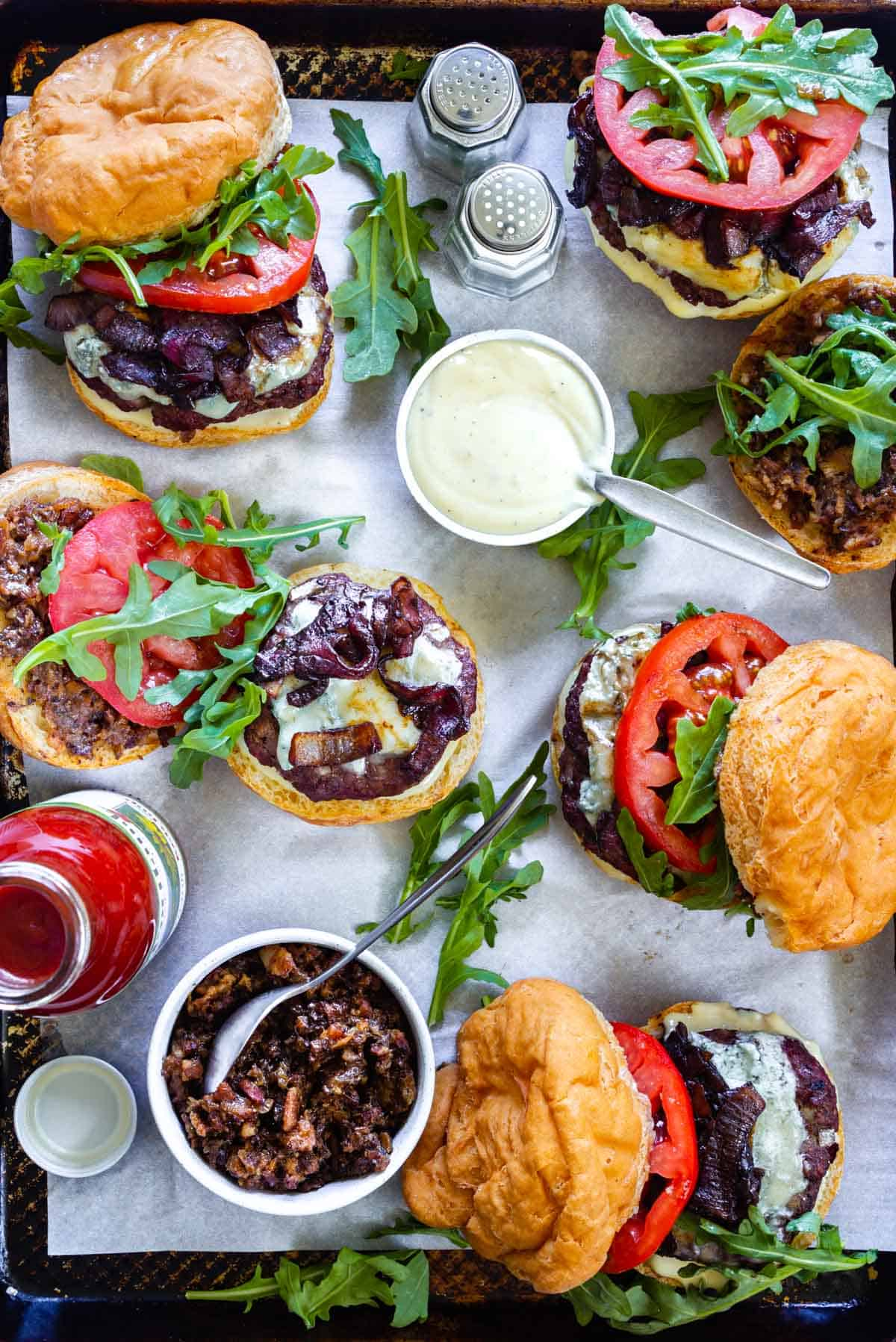 A zoomed in view of a tray loaded with bacon blue cheese burgers and small side dishes with roasted garlic aioli and bacon jam. A salt and pepper shaker and a ketchup bottle also accompany the burgers.