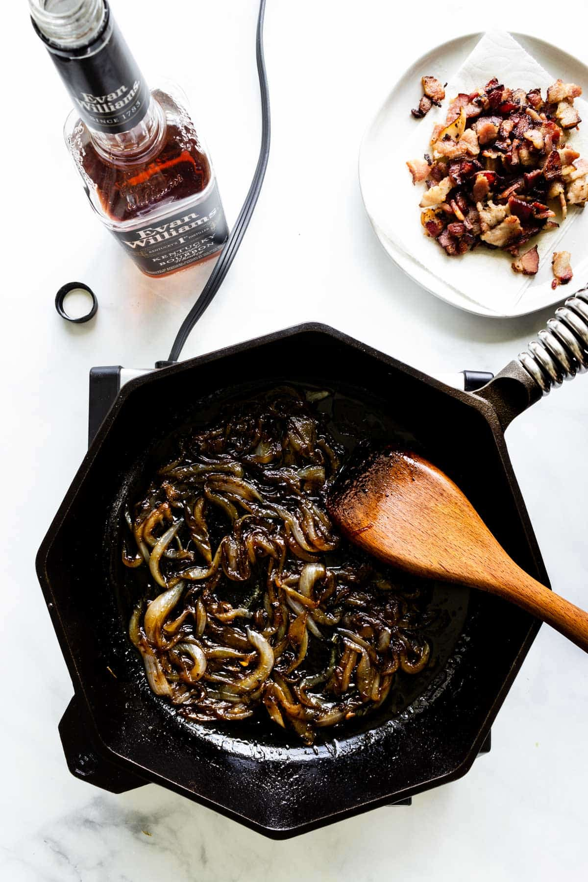 Sweet onions slowly caramelize in a cast iron skillet. A plate of cooked, coarsely chopped bacon and a bottle of bourbon sit nearby.