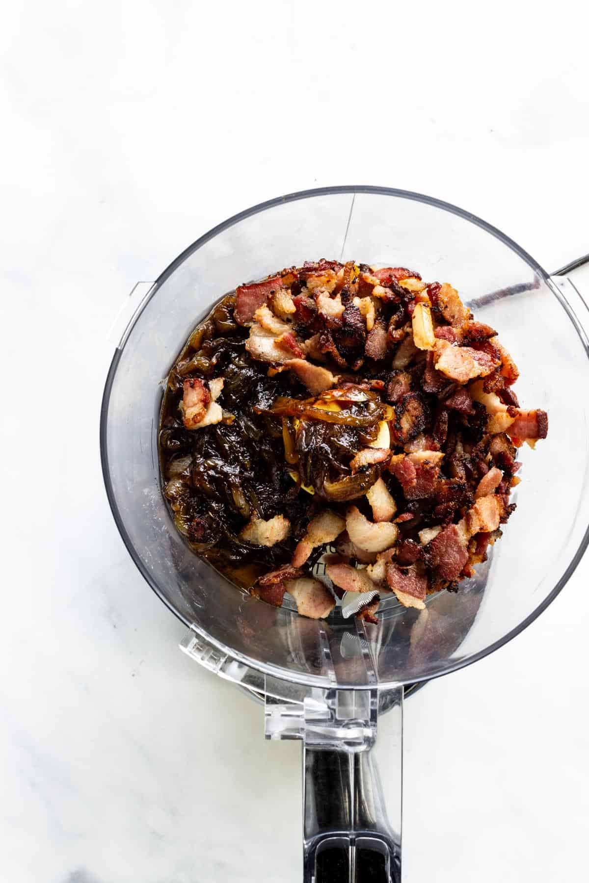 The ingredients for bacon jam are placed in a food processor after they have finished cooking.