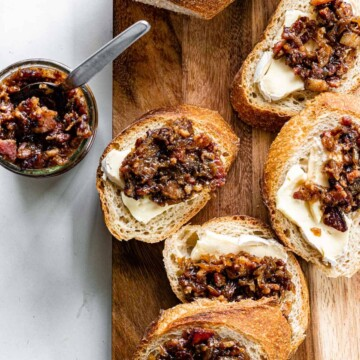 Crostini topped with gorgonzola and bacon jam are arranged on a wooden board. A jar of bacon jam with a spoon sits to the side.