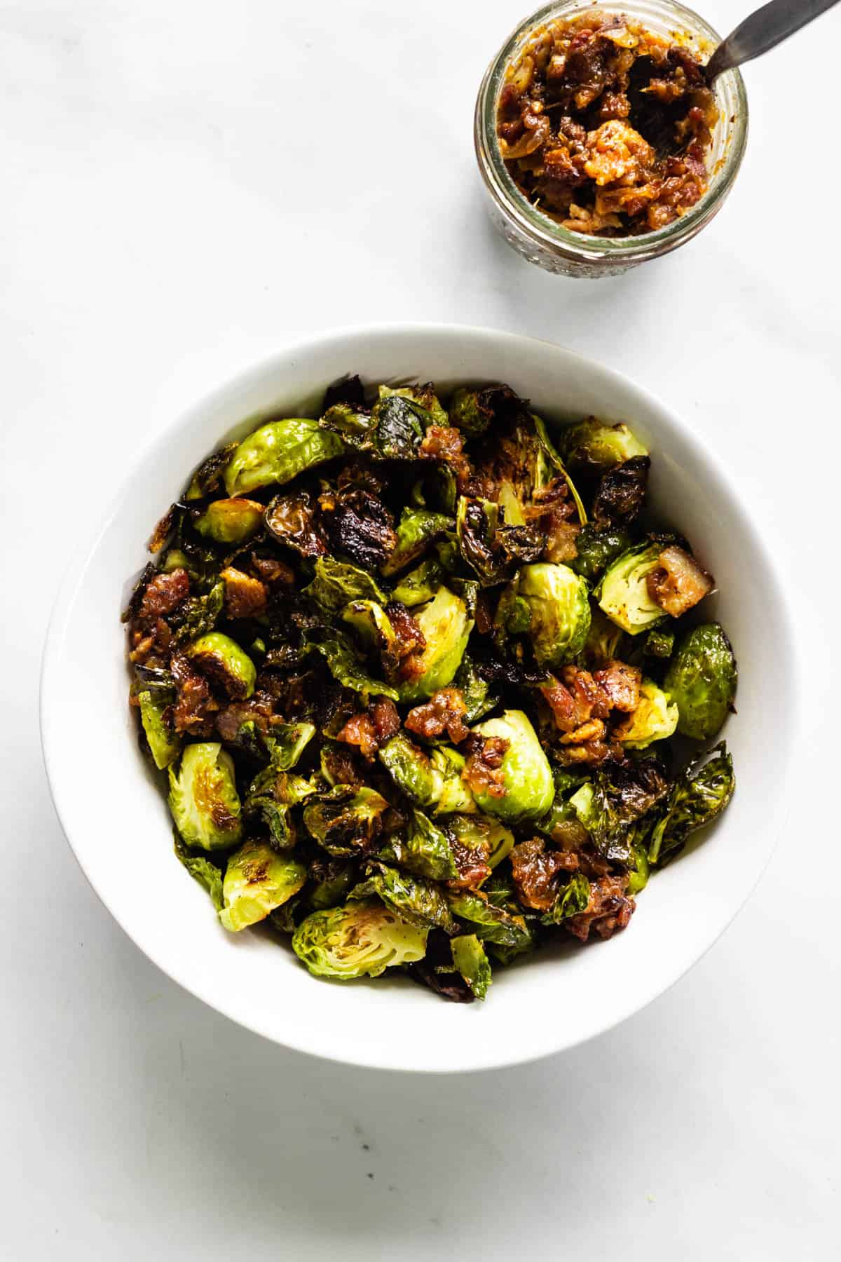 A white bowl with roasted brussels sprouts topped with bacon jam. A jar of bacon jam sits to the side.