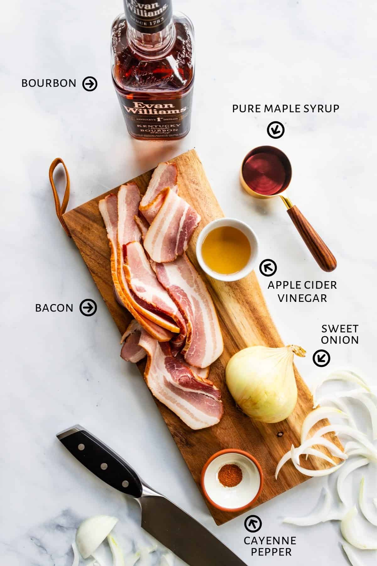 Strips of bacon are laid out on a cutting board with sliced onions. A bottle of bourbon, a pinch bowl of cayenne, a small cup of apple cider vinegar, and a measuring cup with maple syrup sit around the cutting board.
