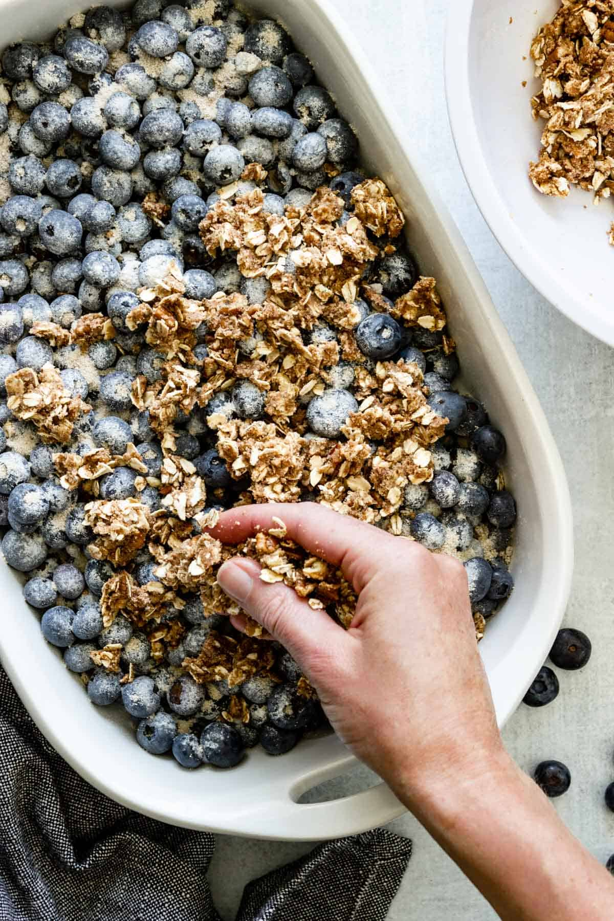 A hand is sprinkling crisp topping over a baking dish of blueberries.