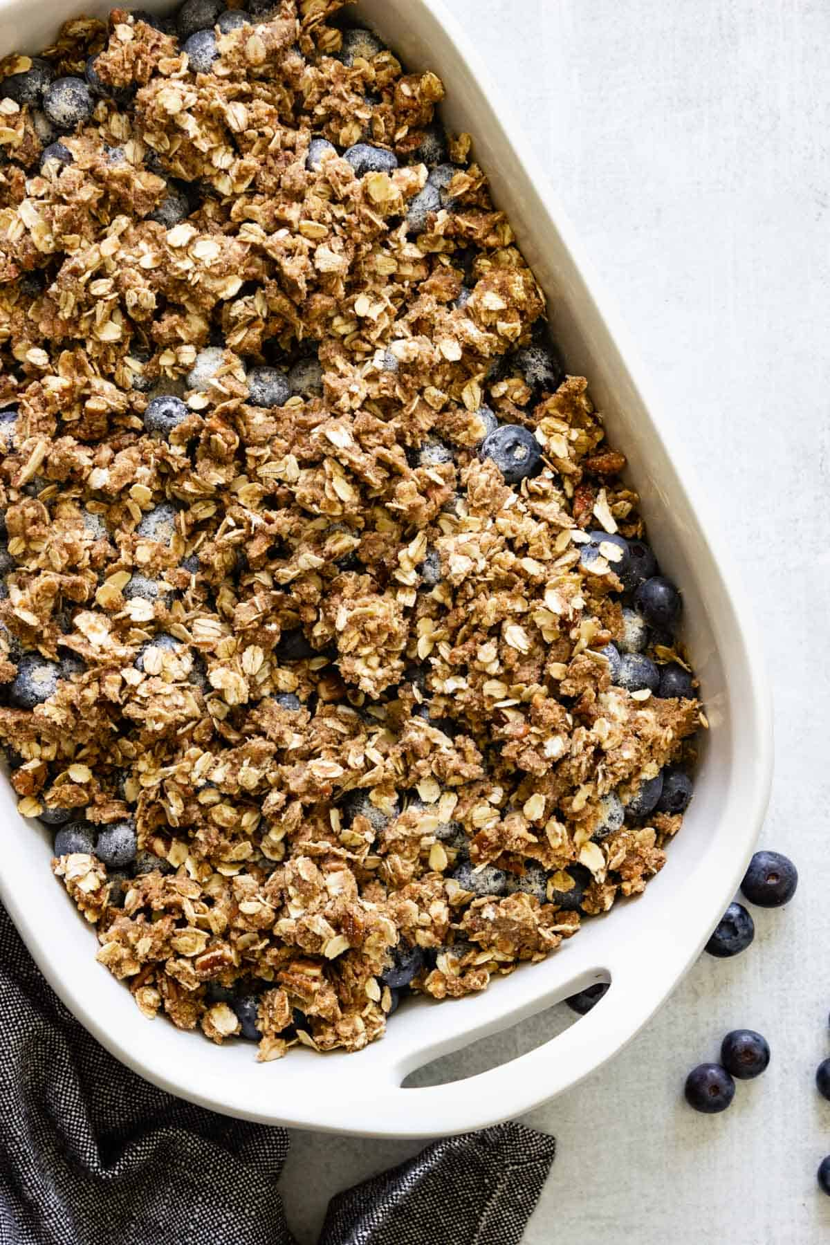 A white baking dish with fresh blueberries is topped with crisp topping and is ready to go in the oven.