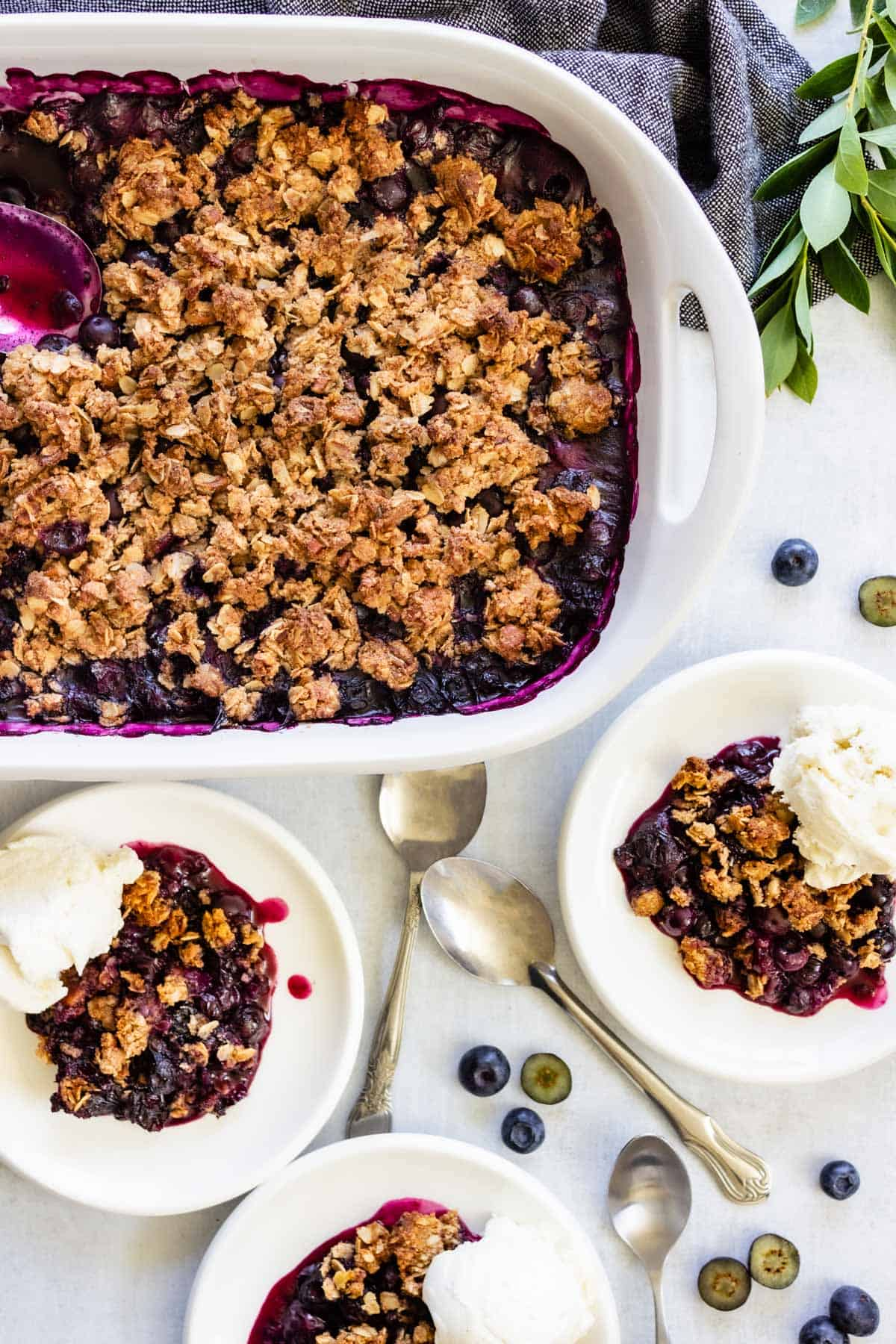 Three plates of blueberry crisp are served with a scoop of vanilla ice cream. Some fresh blueberries and several spoons are scattered next to them.