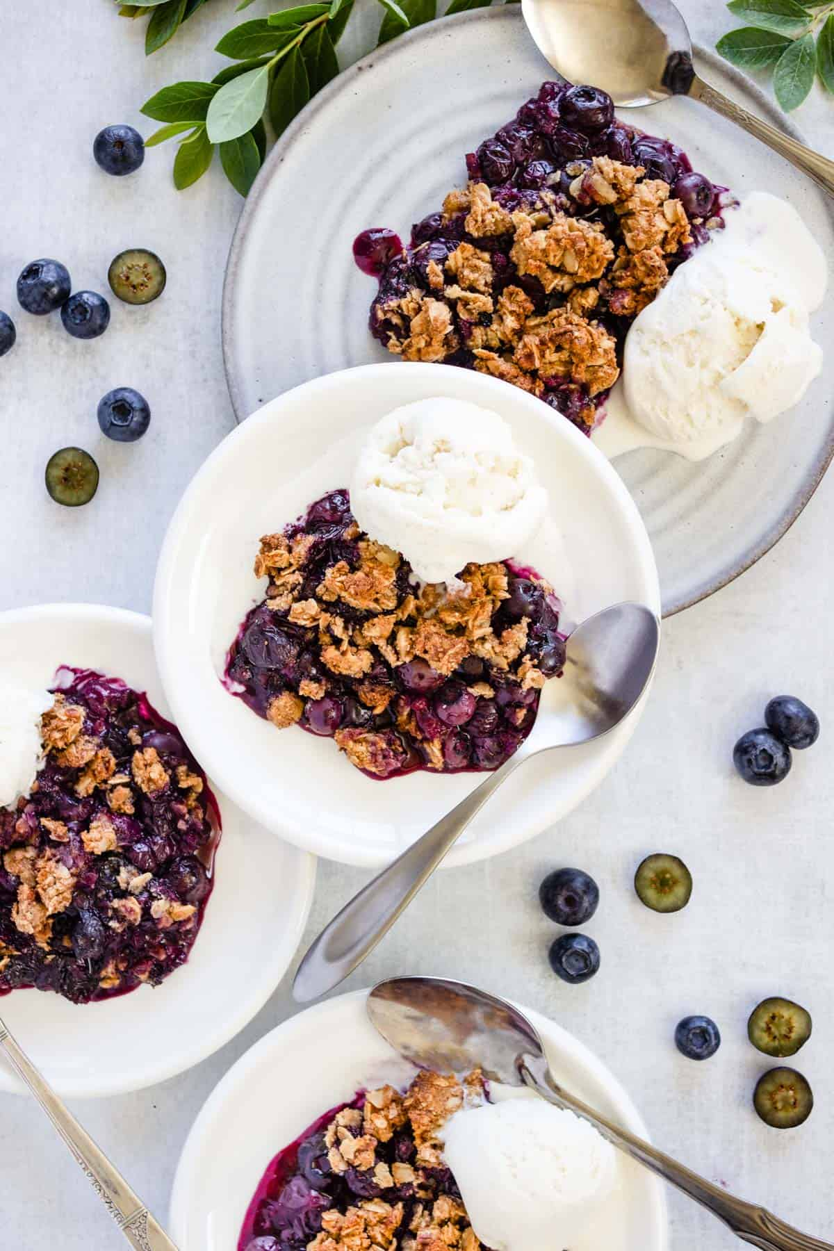 Four plates with blueberry crisp are topped with vanilla ice cream and ready to be served.