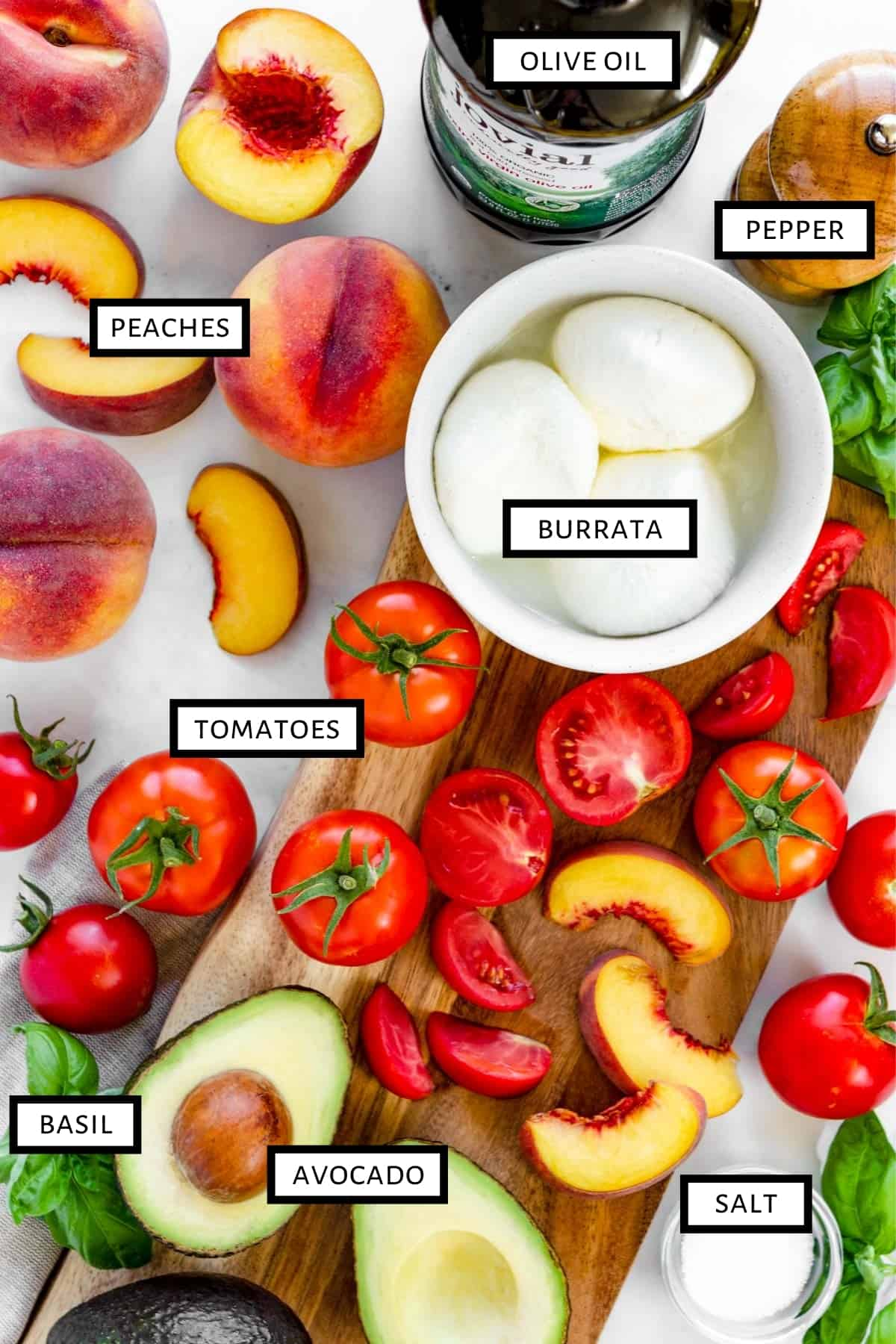Ingredients for a Peach Caprese Salad are spread out on a cutting board and marble countertop.