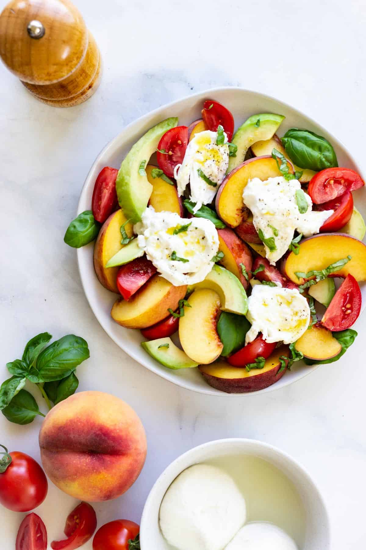 A peach caprese salad sits on a marble countertop next to a small bowl of burrata, a pepper grinder, some fresh basil leaves, and a peach.