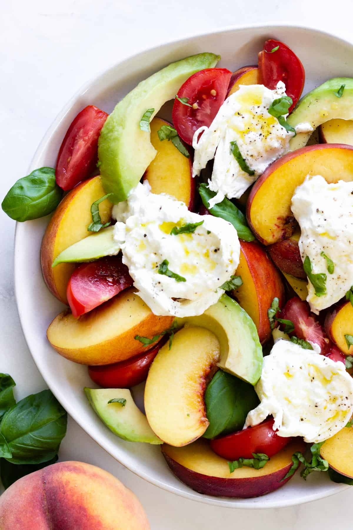 A white plate with Peach Caprese Salad on a marble countertop. A peach and fresh basil sit nearby.