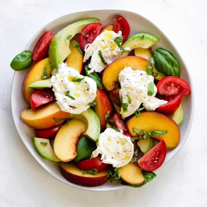 Slices of peach, tomato, and avocado are topped with burrata, basil and olive oil.