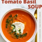 A white bowl of roasted red pepper tomato basil soup topped with burrata, fresh basil and a swirl of pesto with a gold spoon.