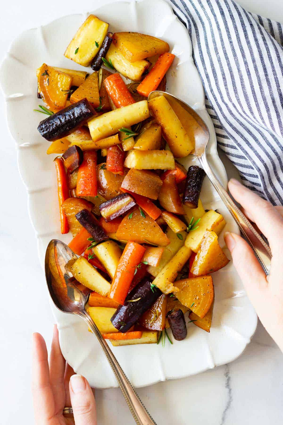 Two hands reach for serving utensils to serve veggies on a platter.