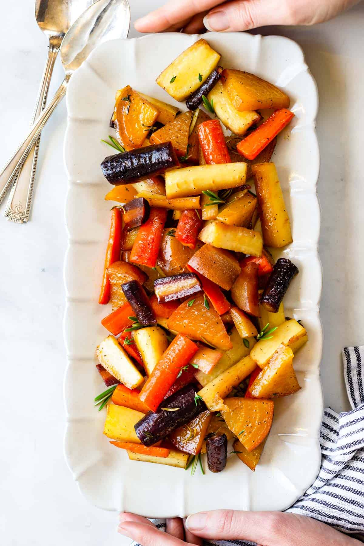 Two hands are serving a platter of roasted vegetables.
