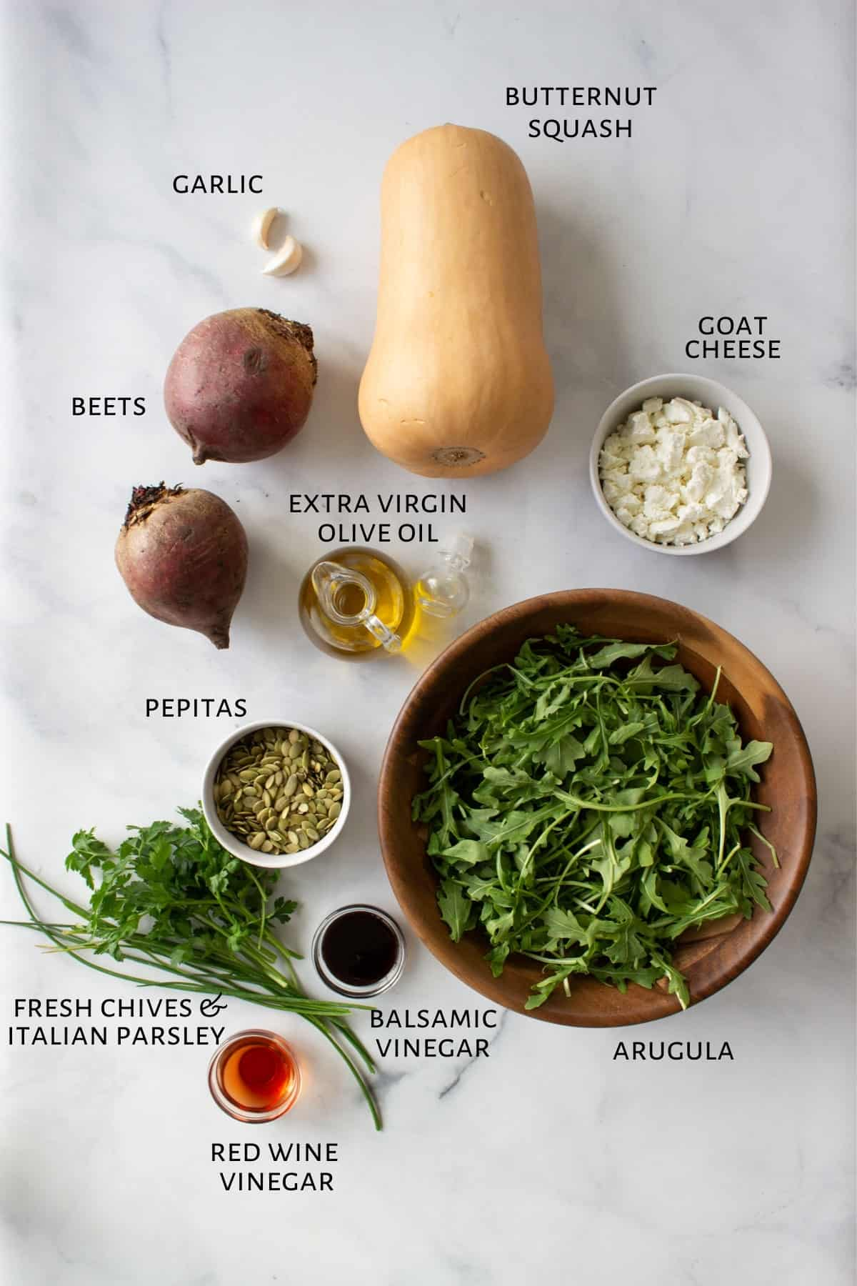 Ingredients for a salad are laid out on a marble countertop.