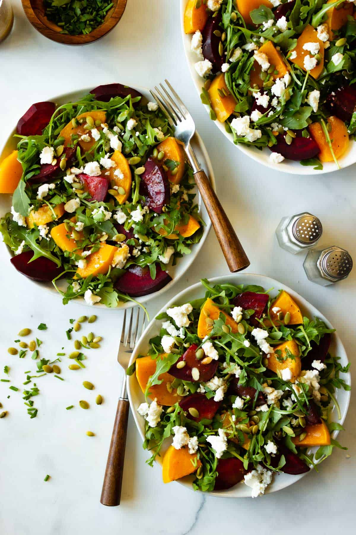 Two servings of beet and butternut squash salad with wooden handled forks.