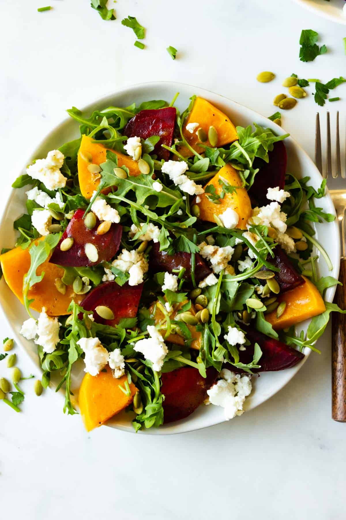 A plate of roasted beet and buttenrut squash salad with a wooden handled spoon resting next to it.