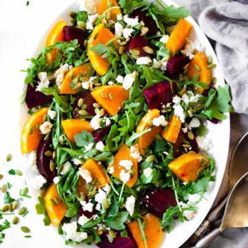 Arugula is topped with roasted beets and butternut squash and served on a white platter.
