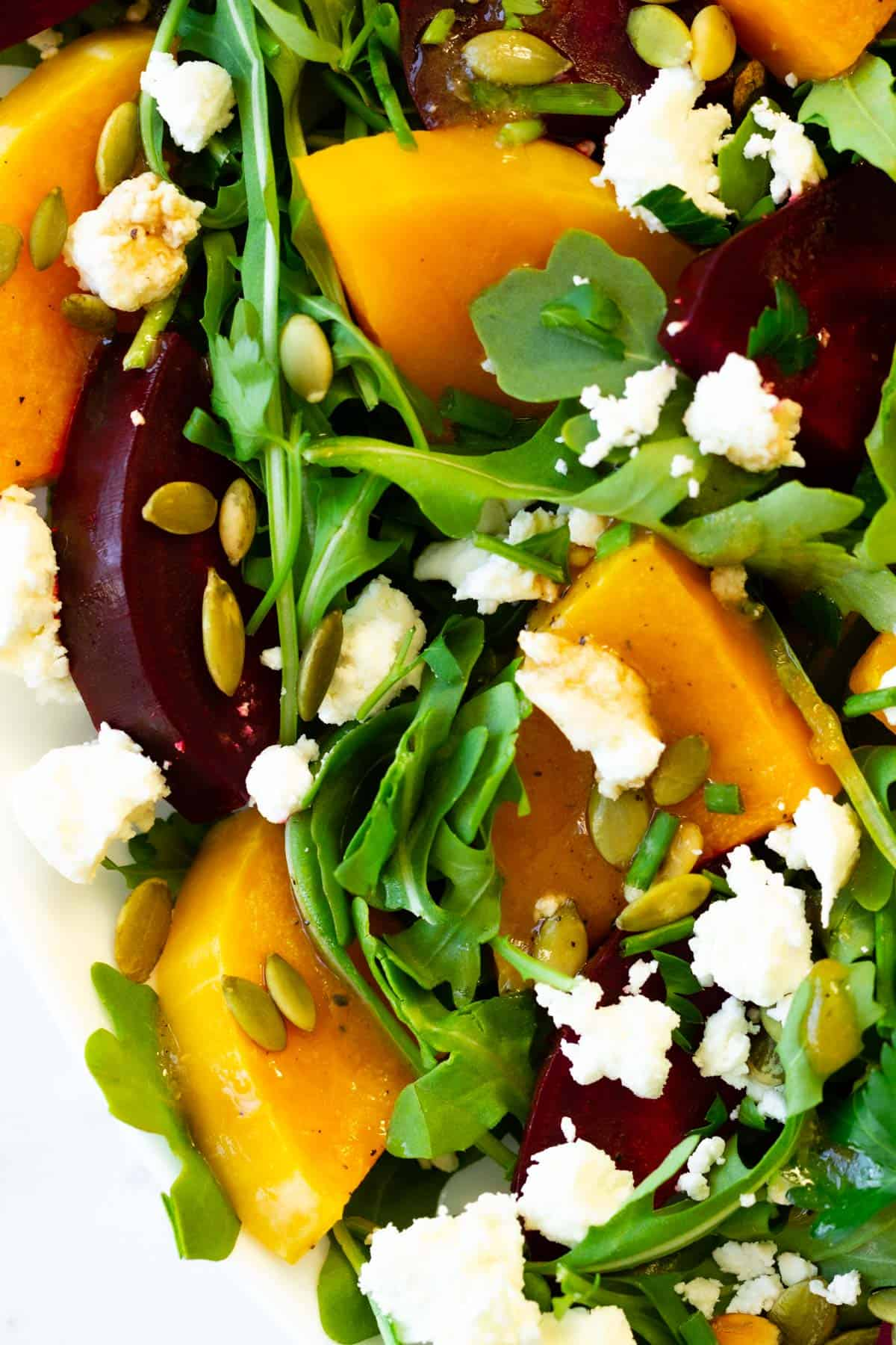 Sliced roasted beets and butternut squash with arugula, pepitas, and cheese.