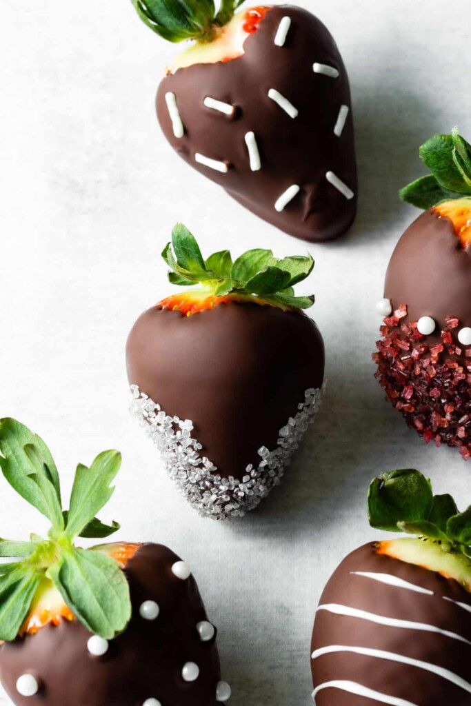 Chocolate covered strawberries are decorated with different sprinkles.