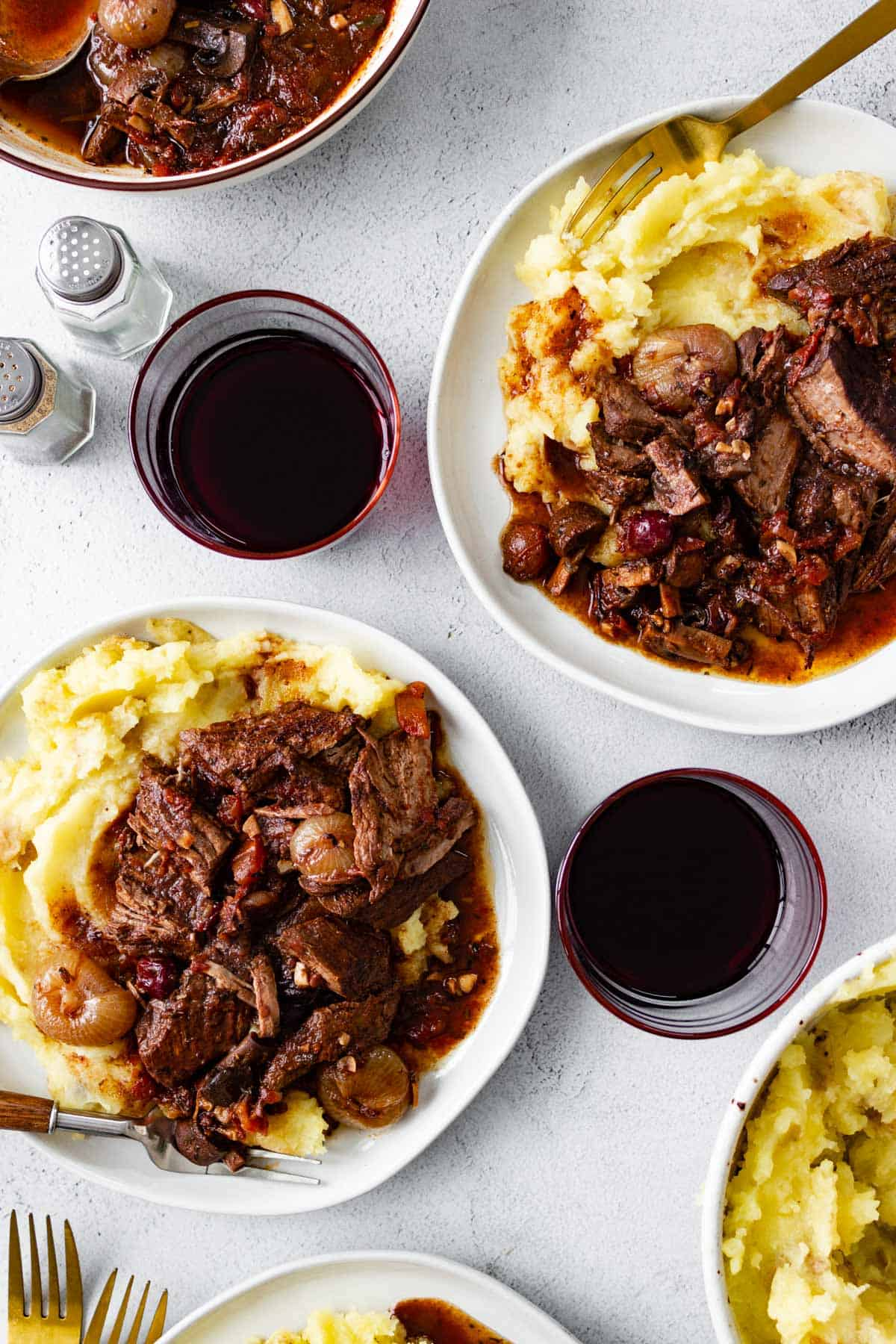 Plates of mashed potatoes topped with tender ribs in pomegranate sauce.