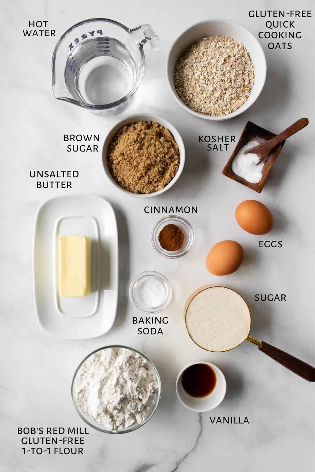 Ingredients to make oatmeal cake are laid out on a marble countertop.