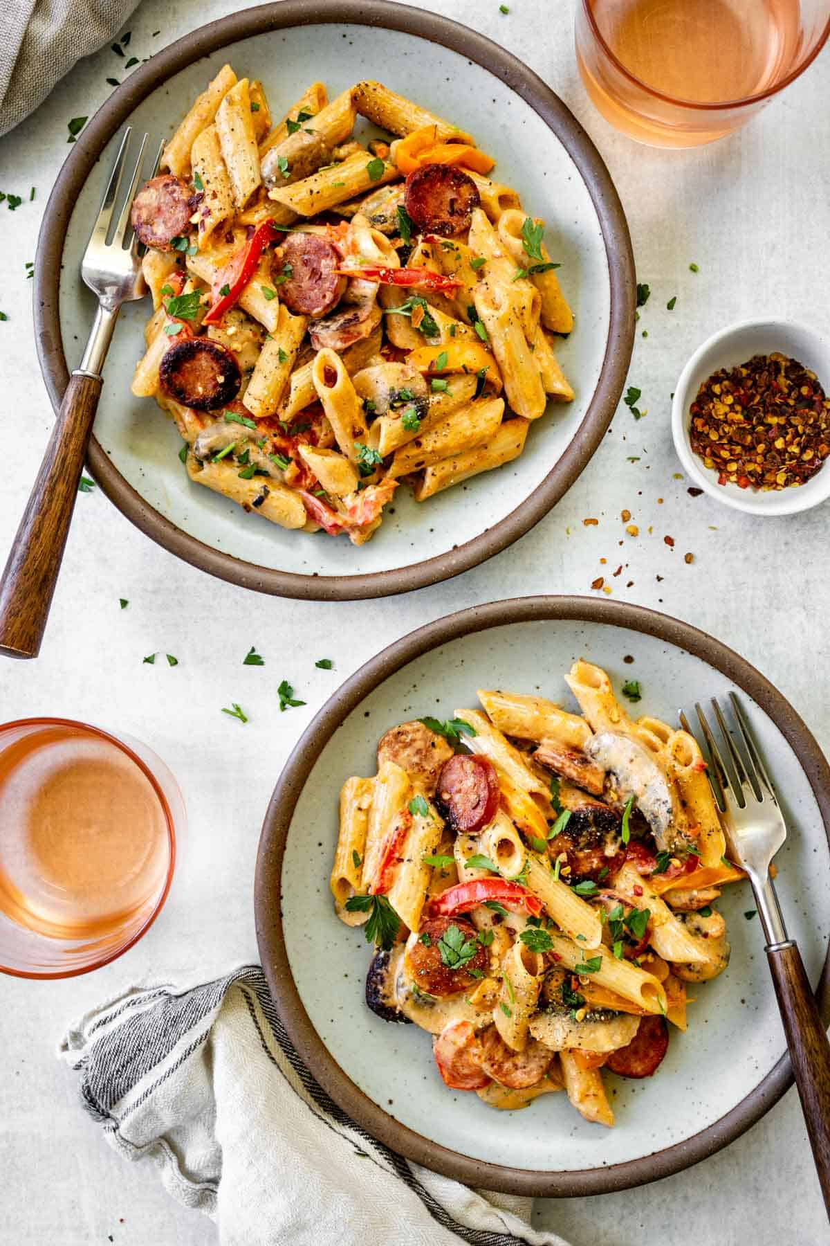 Two plates of creamy cajun pasta are served with two glasses of wine.
