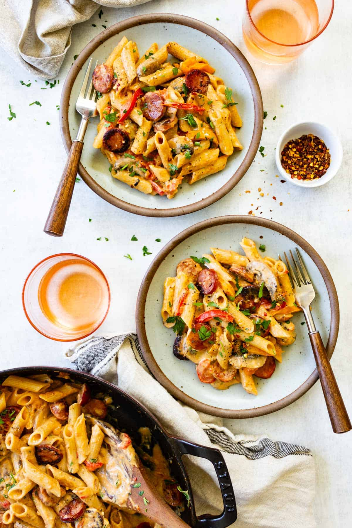 A large skillet of cajun pasta sits on a table with a couple of servings of the meal.