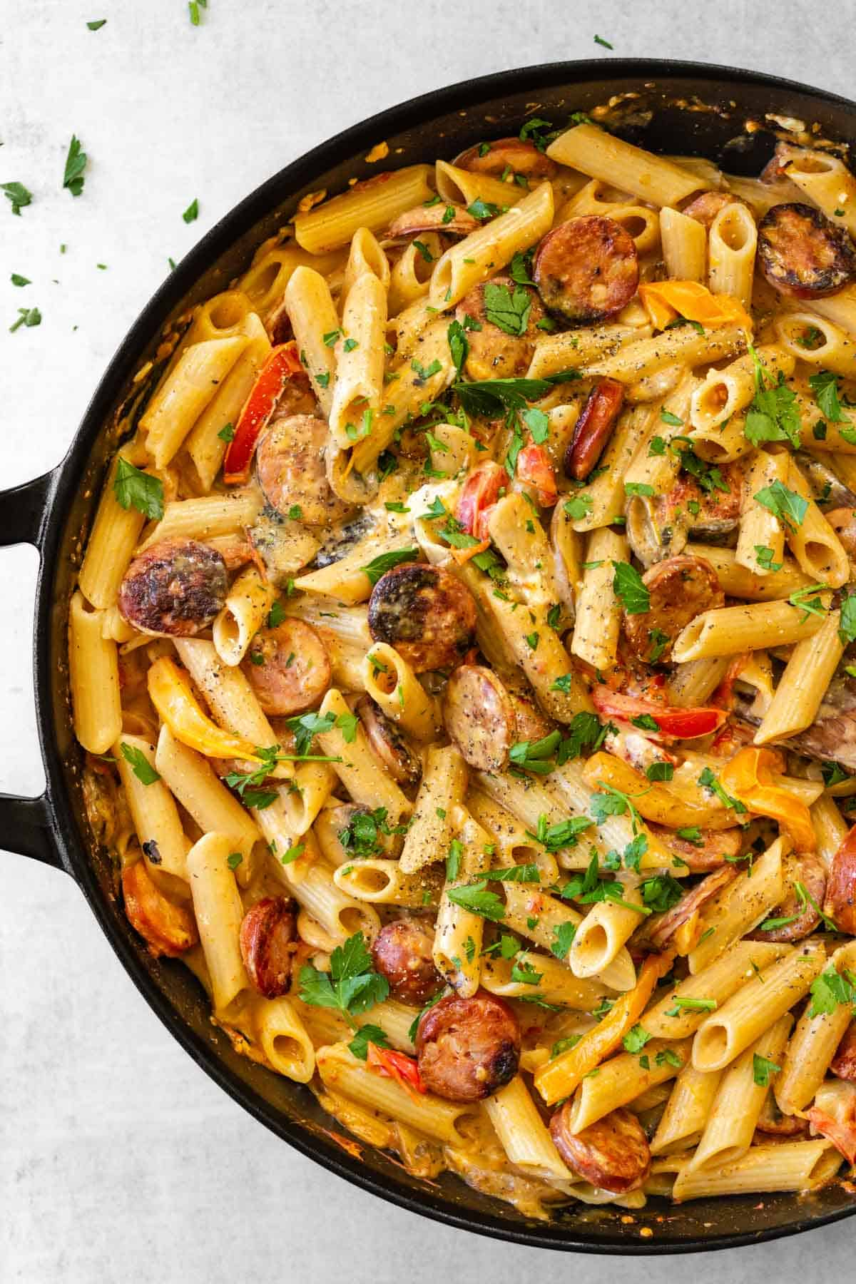 A large skillet of creamy cajun pasta with sausage, bell peppers, and mushrooms.